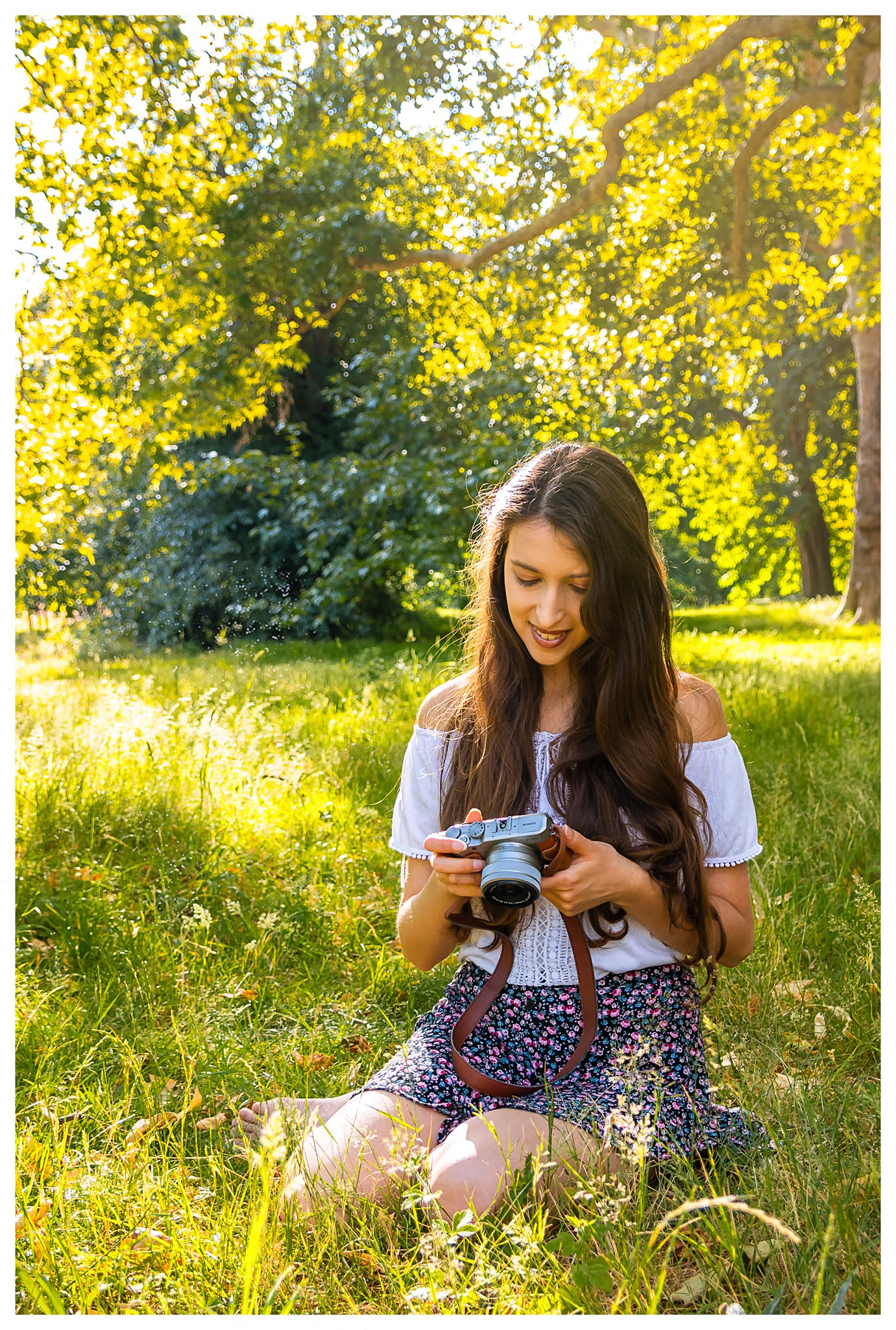 - Woman holding a camera in the park Portrait of Monamour Photography