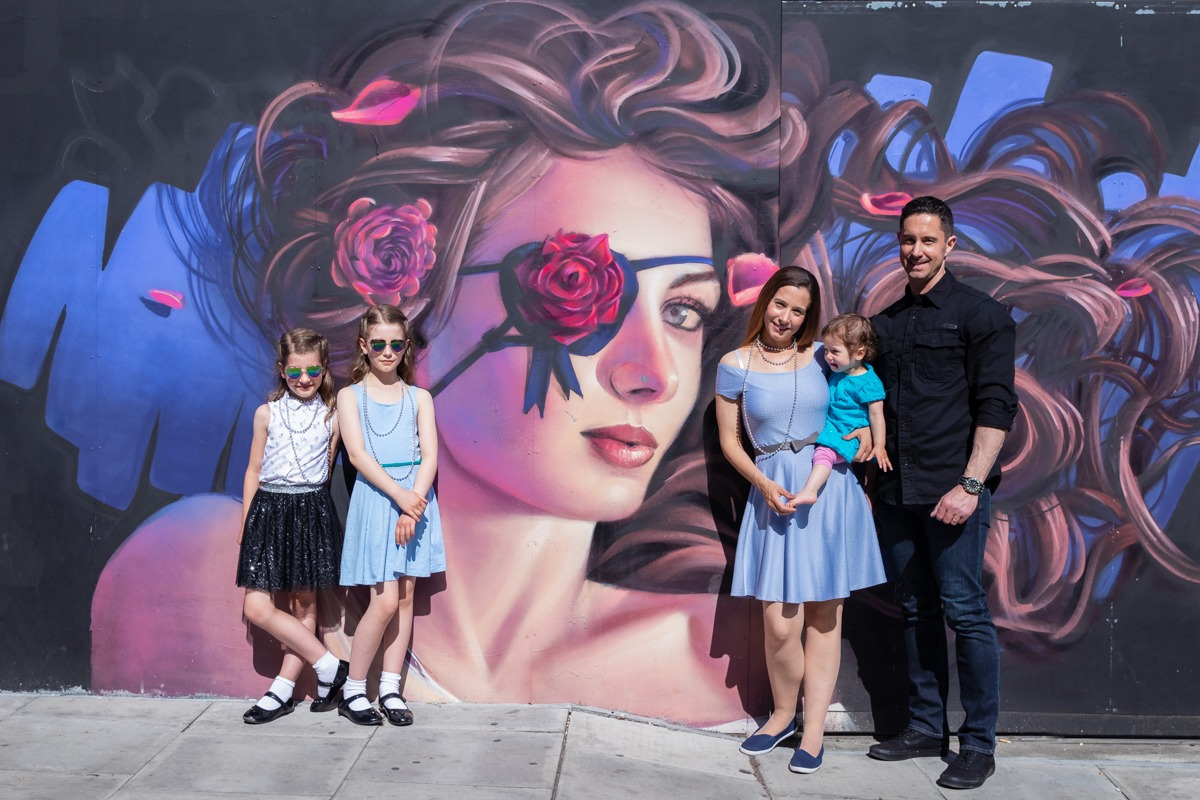 Family Photoshoot - Beautiful family in front of a graffiti of woman and flowers wall in Camden Town, London